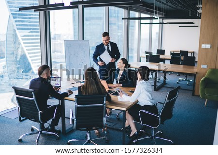 Adult entrepreneur in formal wear standing in conference room and talking with colleagues sitting at table while discussing strategies of company