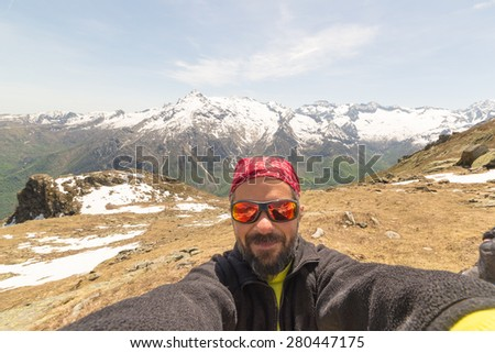 Adult european hiker with sunglasses and beard taking selfie in springtime with the beautiful snowcapped italian Alps in the background. Natural warm tones, low contrast, wide angle view. #280447175