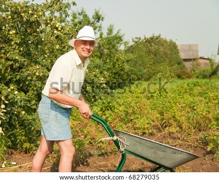 stock photo : Adult farmer standing in farm field with barrow