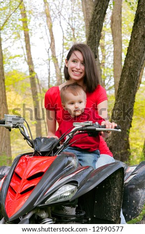 adult female and young male child riding on a four wheel all terrain vehicle in the woods