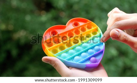 Adult female hand playing rainbow toy pop it toy simple dimple. Anti Stress Sensory Toy. Colorful antistress sensory heart-shaped toy fidget push pop it on green nature background. Trend 2021.