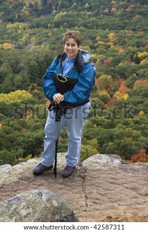Adult female hiker standing at the edge of a  cliff high above forest