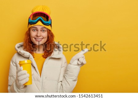 Adult female snowboarder with ginger hair, enjoys hot bevergae during winter time, wears ski clothing, points away on free space for your promotional content or text. People and vacation concept