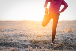 Adult fitness sportswoman runner stretching legs before run on field. Exercise on a sunny frosty morning.