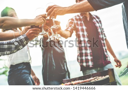 Adult friends cheering with wine at barbecue outdoor - Group of people having fun drinking wine in vineyard at sunset outside - Friendship, summer lifestyle and party concept - Focus on right top hand