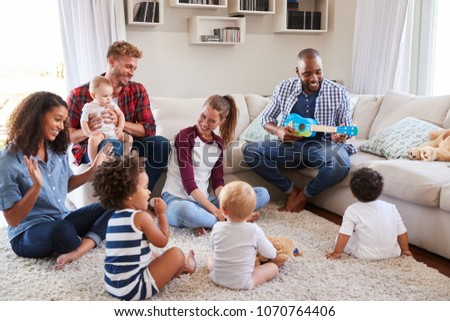 Adult friends entertaining their toddlers in sitting room