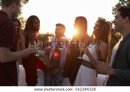 Adult friends socialising at a party on a rooftop at sunset #562284328