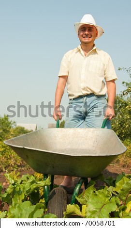 Adult gardener Holding  agricultural equipment in summer time