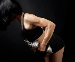 adult girl with black hair is dressed in a sports bra and short shorts is doing physical exercises on the arm muscles with a steel dial dumbbell, low key