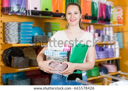 Adult girl with disposable tableware in her hands chooses disposable tableware in store #665578426