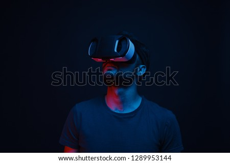 Adult guy in modern VR glasses looking away while standing in dark room and exploring virtual reality #1289953144