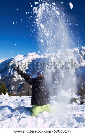 Adult guy throwing snow in the air in high mountains