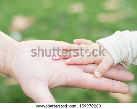 adult hand holding a child\'s hand with a wooden heart