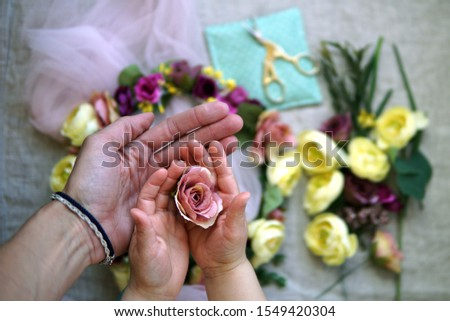 Adult hand touches baby palms that hold a rosebud; ranunculuses, green, gold scissors on a mint pillow and flower wreath are on grey linen background #1549420304