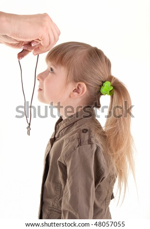 stock photo : Adult hands puts on a little girl Christian cross