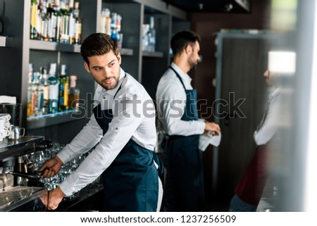 adult handsome barista in apron using coffee machine at workplace #1237256509