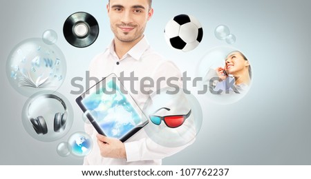 Adult handsome man holding tablet computer. Icons of different object are flying around. All multimedia in one mobile gadget concept