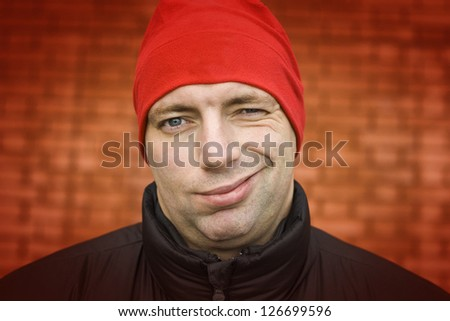 adult handsome man in red hat winking