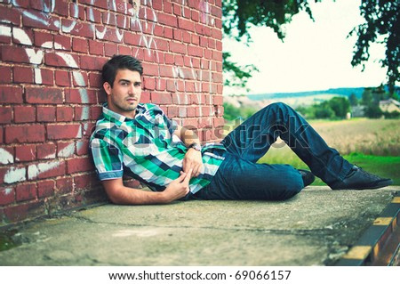adult handsome man posing outdoor in a graffiti wall background