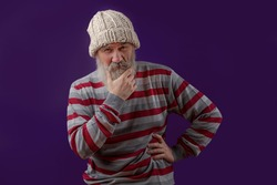 Adult handsome senior male model in a knitted hat-wearing striped sweater perplexed holding his gray beard on purple background. Old man character showing emotions of suspicion, criticism, distrust.