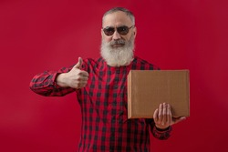 Adult handsome senior male model with a gray beard wearing checkered red and black shirt showing thumb up, looks confidently, holding a cardboard delivery box. Mock up. Red isolated background