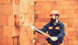 Adult handsome worker builder using hammer and smash tool at construction site. Man using sledge-hammer. Labor are using hammer smash destroy cement wall