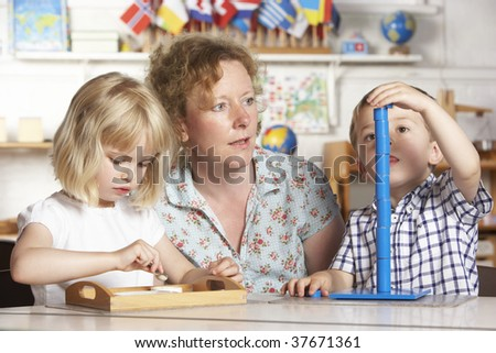 Adult Helping Two Young Children at Montessori/Pre-Scho ol - stock photo