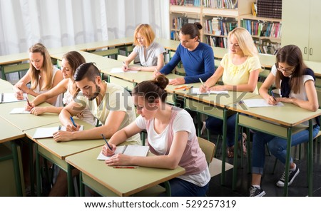 Adult highschool students learning in classroom at their desks