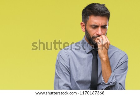 Adult hispanic business man over isolated background looking stressed and nervous with hands on mouth biting nails. Anxiety problem.