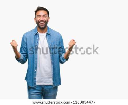Adult hispanic man over isolated background celebrating surprised and amazed for success with arms raised and open eyes. Winner concept.