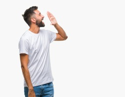 Adult hispanic man over isolated background shouting and screaming loud to side with hand on mouth. Communication concept.