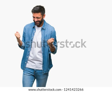 Adult hispanic man over isolated background very happy and excited doing winner gesture with arms raised, smiling and screaming for success. Celebration concept. #1241423266