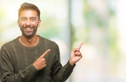 Adult hispanic man wearing winter sweater over isolated background smiling and looking at the camera pointing with two hands and fingers to the side.