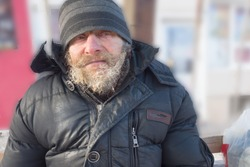 adult homeless man sits on a bench on a winter day