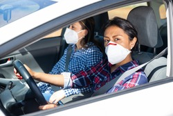 Adult Latin American woman in protective face mask driving car with girl in passenger seat. Concept of individual precautions during Covid 19 pandemic