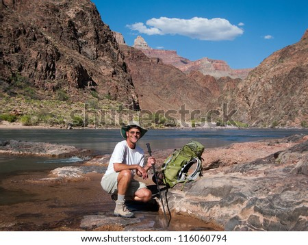 Adult male backpacker at the bottom of the Grand Canyon beside the Colorado River