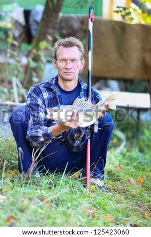 Adult male fisherman with a catch in his hands in outdoors. - stock photo