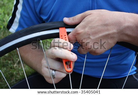 Adult male in the process of changing his flat bike tire