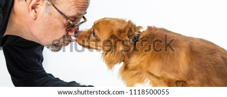 Adult male kissing sweet small crossbreed dog over a white horizontal web banner or social media cover photo