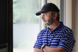 Adult male looking out a rain covered window might illustrate a recent job loss, unemployment, quarantine, financial or health concerns or stay home, shelter in place from Coronavirus