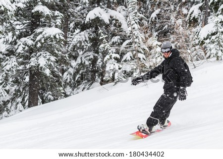 adult male snowboarding in the mountains of northern Idaho in snowy winter conditions