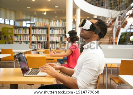 Adult male student training with VR simulator in library. Man wearing virtual reality glasses, sitting at desk with laptop, touching air. Simulation concept
