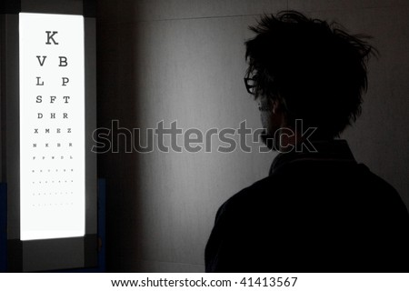 adult male views lit eye chart in dark room - stock photo