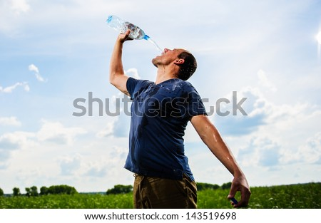 Adult mam plays with water among green field.