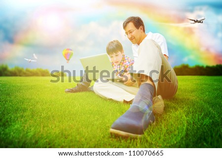 Adult man and his little son sitting on a grass at park and having fun or educating on laptop. Idyllic background - bright future concept