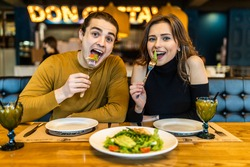 Adult man and woman in casual clothes eating in cafe and smiling to each other