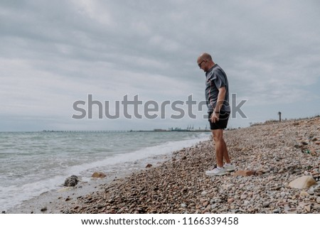Adult man athlete walking on the beach #1166339458
