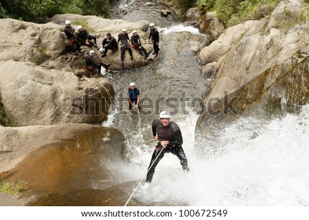 adult man desceding an ecuadorian waterfall in a corect position