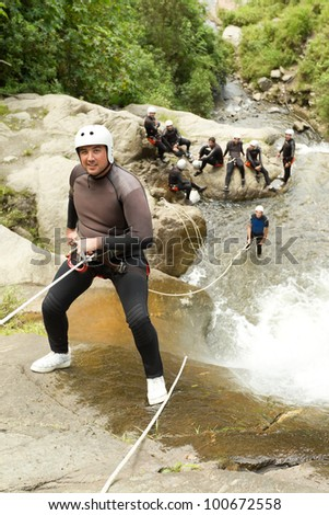 ADULT MAN DESCENDING AN ECUADORIAN WATERFALL IN A CORRECT POSITION