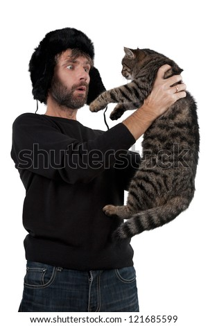 adult man in hat ear flaps holding cat isolated white